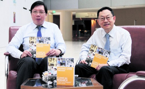 Associate Professor Teoh Yee Leong (left) and Professor Woo Keng Thye with copies of Saving Lives Through Clinical Research: A 50-Year Journey of Singapore's Scientific Leadership, which was commissioned by the Singapore Clinical Research Institute.
